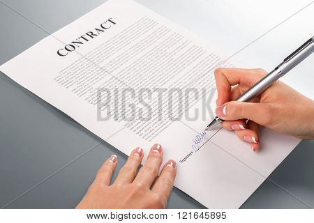 Lady's hand signing promotion contract.