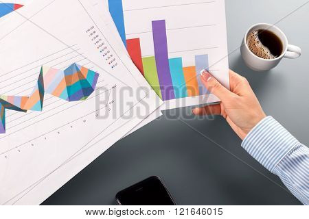 Female clerk's hands holding charts.