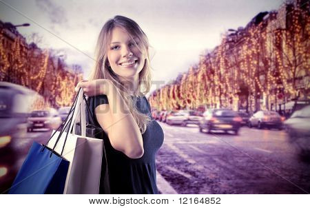 Smiling beautiful woman doing shopping on the Champs-Elysées in Paris