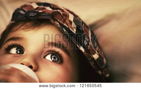 Closeup portrait of cute little baby boy lying down on the bed at home and drinking milk from the bottle, healthy tasty child's nutrition
