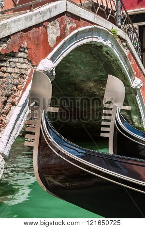 Close Up Of Two Gondola's Iron Prow And Antique Bridge In Venice, Italy