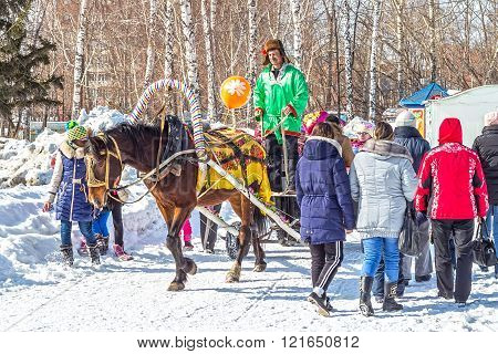 Berdsk Novosibirsk region Siberia Russia - March 13 2016: Russian holiday Maslenitsa ( farewell to winter welcoming the spring ). Horse riding children in the city Park