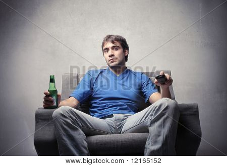 Man sitting on an armchair and holding a remote control and a bottle of beer