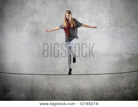 Beautiful woman standing on a rope over the void