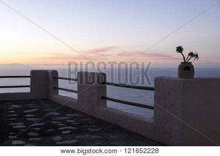 sunset over ocean behind sihouette of balcony parapet on tenerife