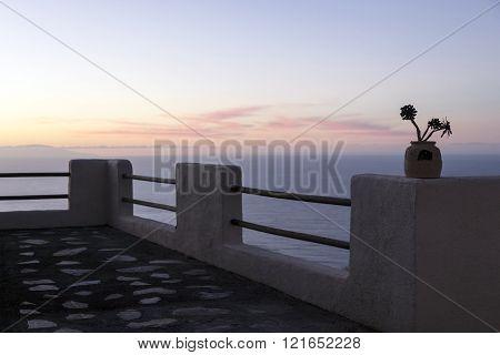 sunset over ocean behind sihouette of balcony parapet on tenerife