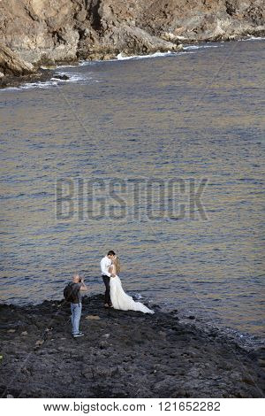 bride and groom on rocky beach of tenerife for wedding picture near the ocean