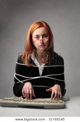 Sad bound businesswoman typing on a keyboard