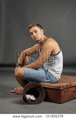 Portrait Of A Man Sitting On A Retro Suitcase