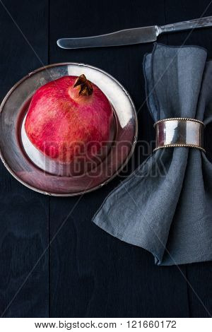 Pomegranate with old vintage dinnerware background vertical
