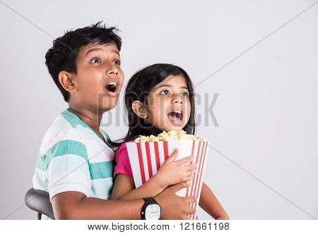 asian little boy and girl watching movie with pop corn, little indian girl sitting with brother watc