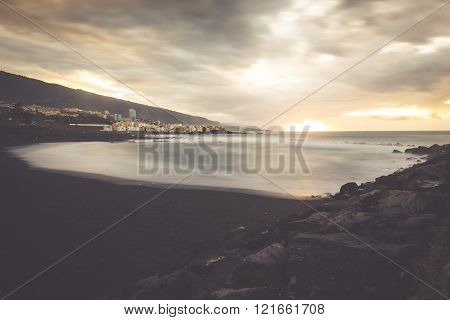 Black Pebble Beach In Puerto De La Cruz By The Sunset , Tenerife, Canary Islands Spain