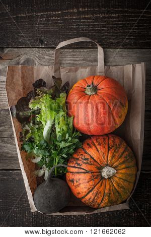 Pumpkins and vegetables inside a paper bag vertical