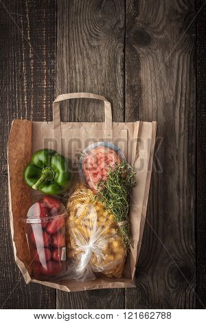 Food mix inside a paper bag on the wooden background vertical