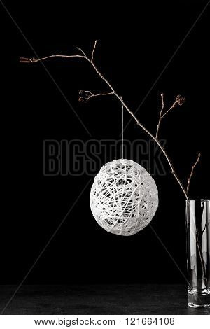 Alder branch in the glass with a white christmas ball on the black stone table vertical