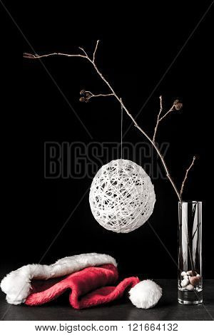 Alder branch in the glass with a white christmas ball and santa claus hat on the black stone table vertical