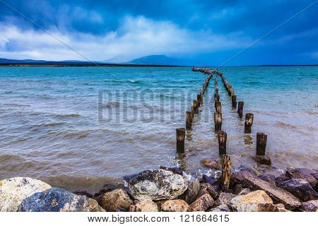Strait of Magellan summer February afternoon. Waterfront, Punta Arenas. From the water stick piles of destroyed pier