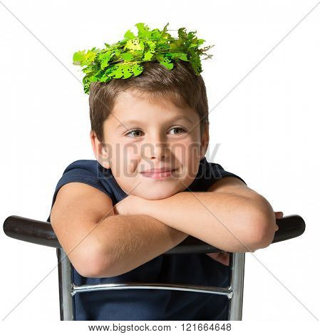 Very beautiful seven year old boy in a carnival wearing a crown of shiny green bats. He sits astride a chair