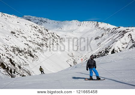 MAYRHOFEN, AUSTRIA :  MARCH 22, 2016:View of  a snowboarder at Mayrhofen Ski resort area with ski lifts, pistes and skiers. Zillertal Alps, Tirol.