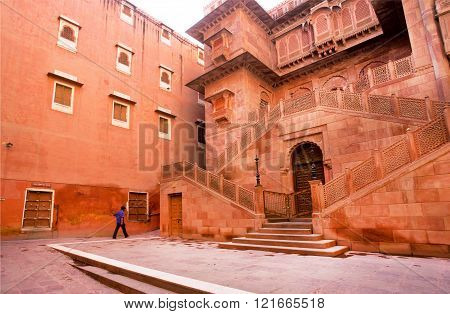 BIKANER, INDIA - MAR 4: Lonely man walking past the main entrance of the 16th century Junagarh Fort on March 4, 2015. The 5.28 hectares large Junagarh fort precinct is studded with palaces and temples