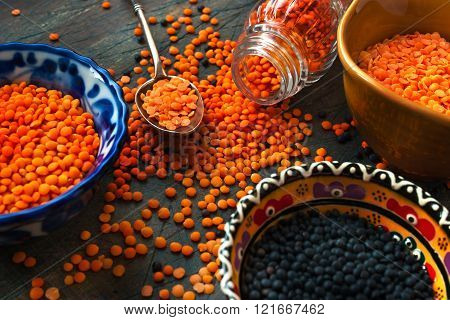Black and red lentil in the colorful ceramic dishes and a metallic spoon on the dark wooden table