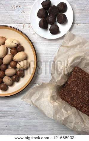 Nuts truffle candy and chocolate cake on the white wooden table vertical
