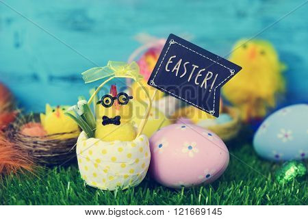 a funny teddy chick, emerging from a dot-patterned eggshell, with a black flag-shaped signboard with the word easter, and some decorated eggs on the grass
