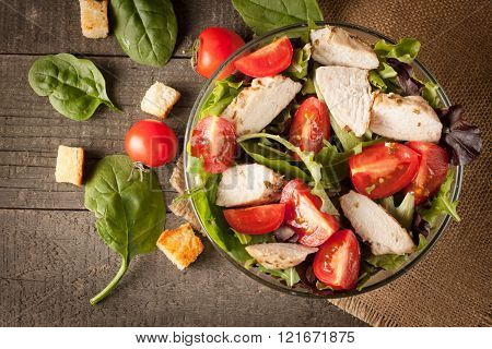 Fresh salad made of tomato, ruccola, chicken breast, arugula, crackers and spices. Caesar salad in a