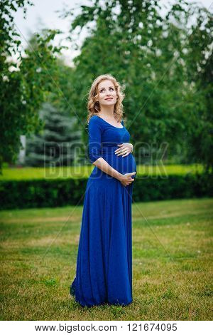 Adorable Young Smiling Pregnant Woman In Blue Dress With Long Blond Curly Hair Holding Her Belly
