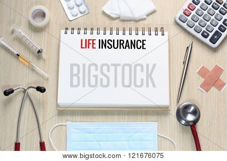 Top view of Life Insurance with notebook stethoscope hypodermic syringe plaster gauze medicine tape and calculator.