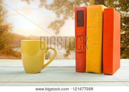 Stack of colorful books and cup on wooden table on natural blurr
