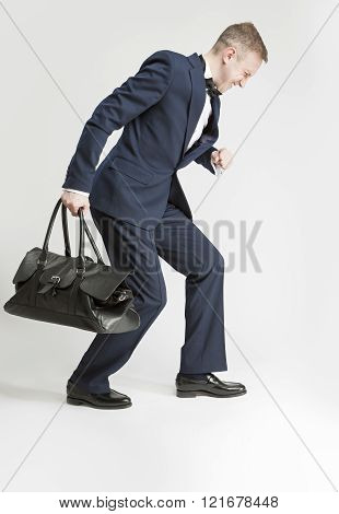 Humorous Concept And Ideas. Handsome Caucasian Man In Official Suit And Bow Tie Hauling Leather Long