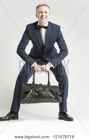 Humorous Concept And Ideas. Handsome Caucasian Man In Official Suit And Bow Tie Trying To Lift Bag.
