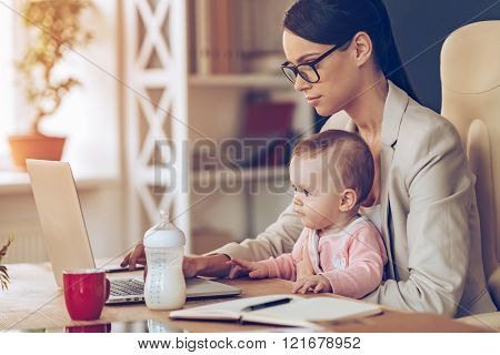 Modern businesswoman can manage everything. Side view of young beautiful businesswoman using laptop while sitting with baby girl on her knees at her working place