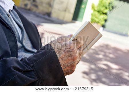 closeup of an old caucasian man reading a book outdoors