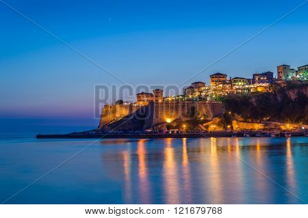 Ulcinj old town fortress at night with silky water and stars on a sky.