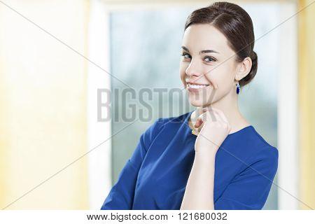 Portrait of Smiling Caucasian Brunette Woman In Stylish Blue Dress Posing Indoors.