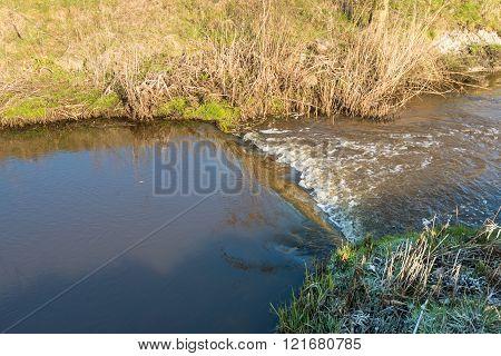 Closeup Of A Small Weir In A Narrow Stream