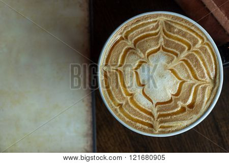 Close up view of hot cappuccino coffee with vintage paper on wooden background