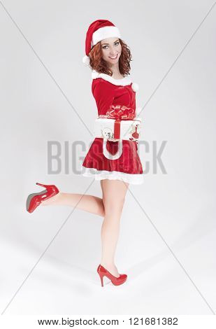 Hot and Sexy Caucasian Female in Santa Hat Holding Gift Box. Isolated on White.