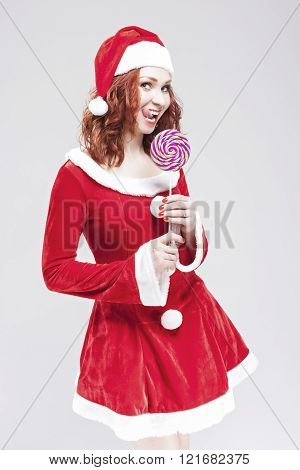 Portrait Of Alluring Caucasian Red Haired Santa Helper With Color Sweet Lollipop Sugar-plum Candy