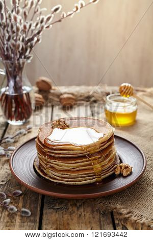 Stack of traditional American pancakes with flowing honey and nuts