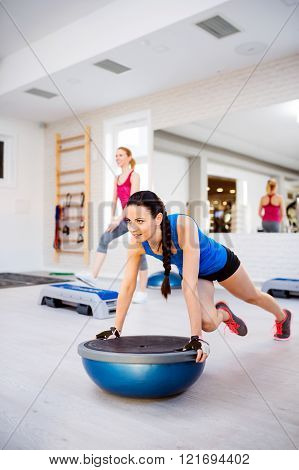 Two fit attractive women in gym doing various exercises