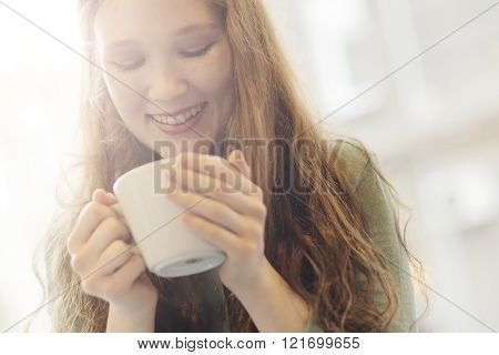 Young girl holding a cup of tea