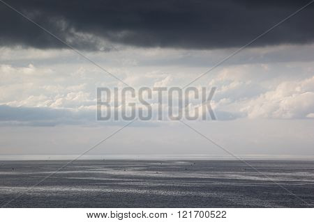The view on a cloudy seascape. Breeze.