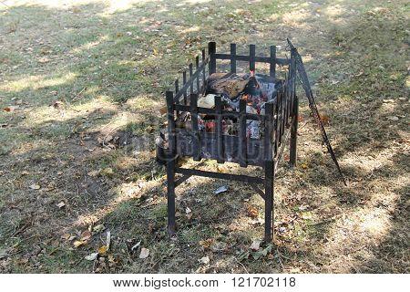 A Metal Framed Outdoor Log Wood Cooking Fire.