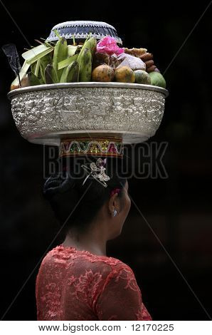 balancing food basket on the head, Balinese woman walks to temple