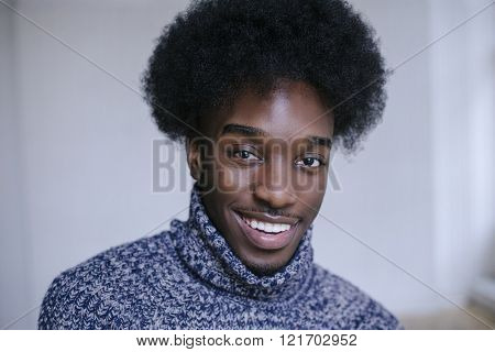 Portrait of a young afroamerican with afro hairstyle, indoors wearing pullover