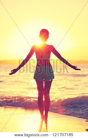 Mindfulness woman practicing yoga sun salutation at beach morning sunrise. Silhouette of fit person standing in sun flare raising arms to the sky with an open heart to do a meditation routine.