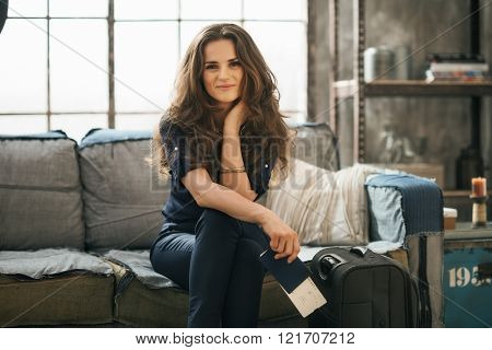 Woman With Luggage In Loft Apartment Waiting For Departure